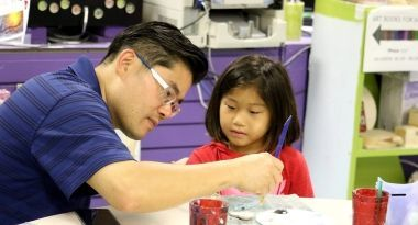 Father and daughter painting in arts & crafts