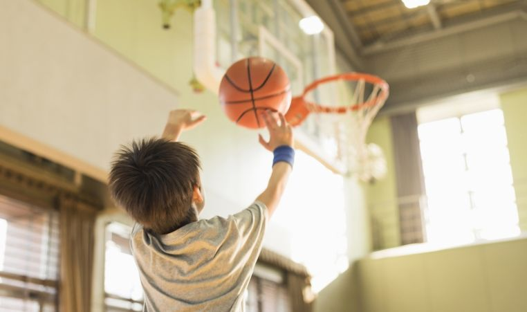 child shooting a basketball